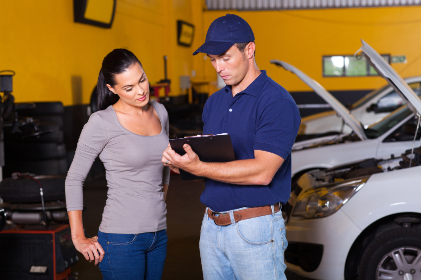auto mechanic and young woman customer in workshop